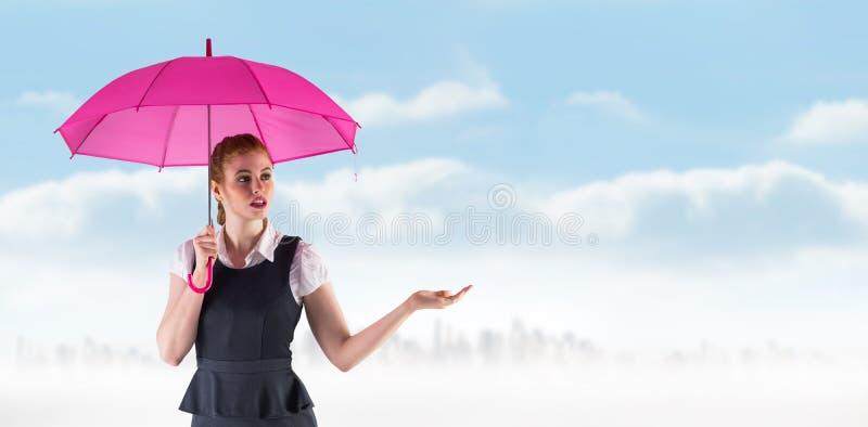 Imagen compuesta de la empresaria bonita del pelirrojo que sostiene el paraguas imagenes de archivo