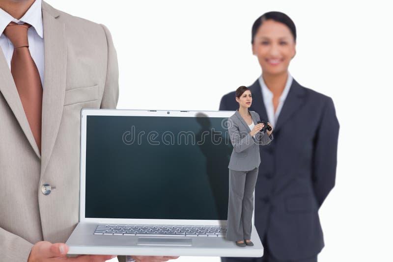 Imagen compuesta de la empresaria joven curiosa con los prismáticos foto de archivo