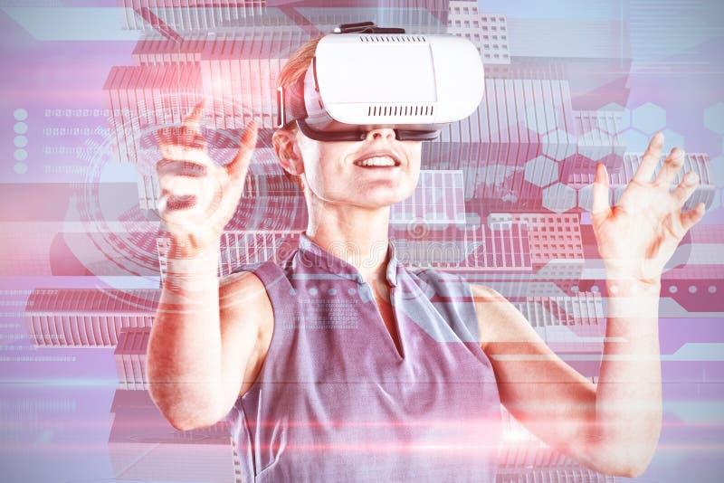Imagen compuesta de la empresaria joven feliz que gesticula mientras que lleva los vidrios de la realidad virtual imágenes de archivo libres de regalías