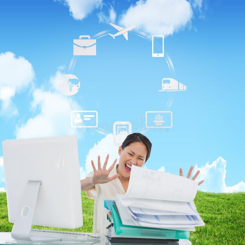 Imagen compuesta de la empresaria que grita con la pila de carpetas en el escritorio fotografía de archivo libre de regalías