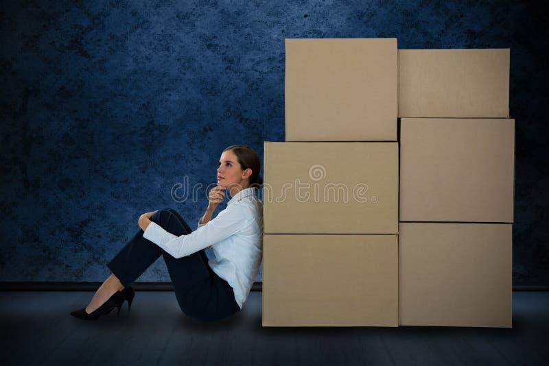Imagen compuesta de la empresaria que se inclina en las cajas de cartón contra el fondo blanco fotos de archivo