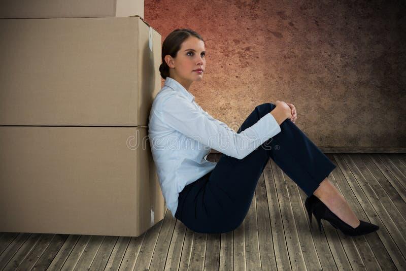 Imagen compuesta de la empresaria que se inclina en las cajas de cartón contra el fondo blanco imagenes de archivo