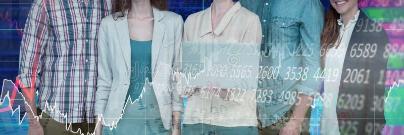Imagen compuesta de la empresaria que sostiene el ordenador portátil mientras que se opone con los colegas al backgro blanco imagenes de archivo