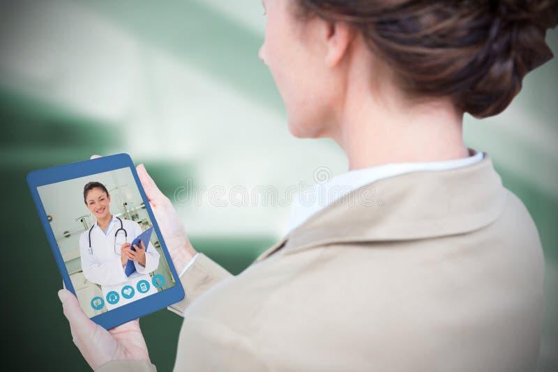 Imagen compuesta de la empresaria que sostiene la tableta digital en el fondo blanco foto de archivo libre de regalías