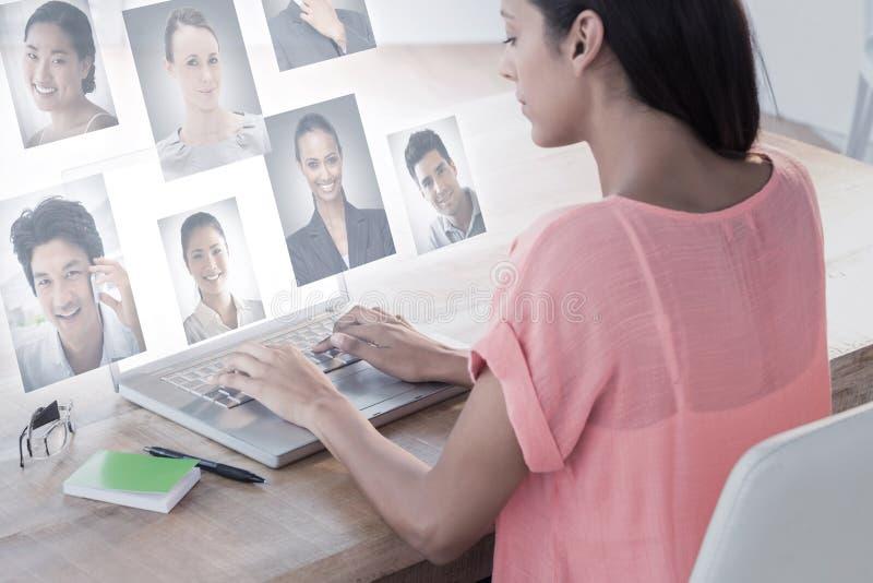 Imagen compuesta de la empresaria que usa el ordenador portátil en el escritorio en oficina creativa foto de archivo