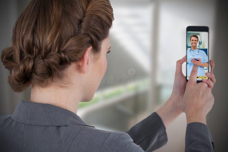 Imagen compuesta de la empresaria que usa el teléfono móvil imágenes de archivo libres de regalías