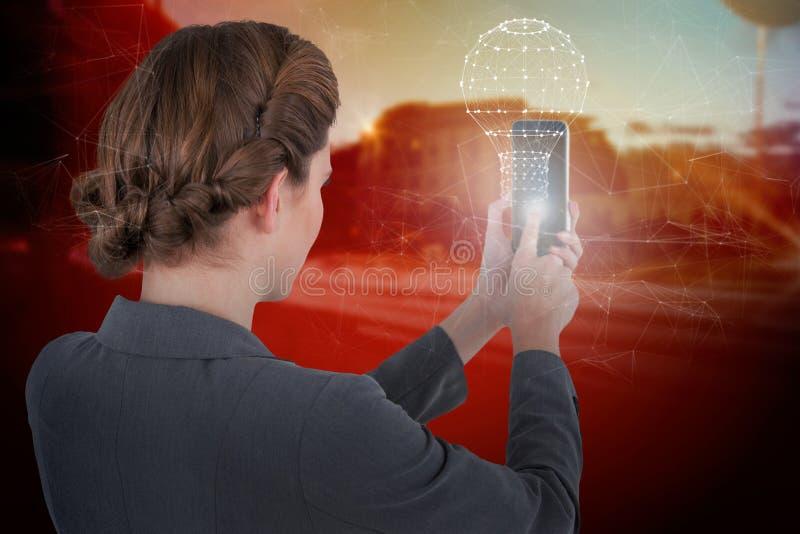 Imagen compuesta de la empresaria que usa el teléfono móvil imagen de archivo