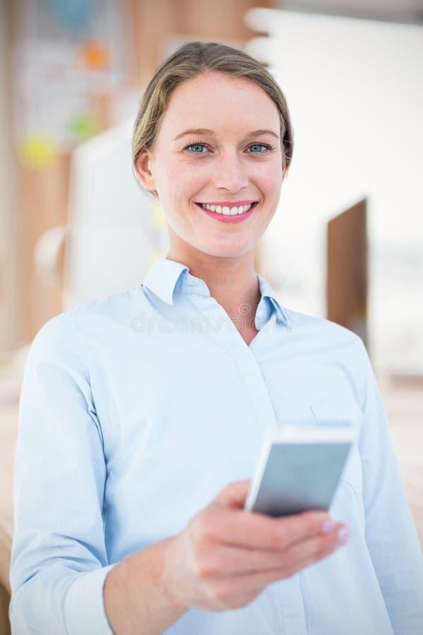 Imagen compuesta de la empresaria que usa su teléfono móvil fotos de archivo