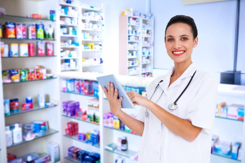 Imagen compuesta de la enfermera bonita que usa la PC de la tableta foto de archivo