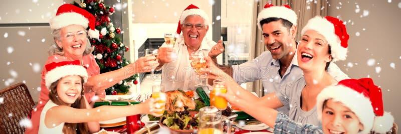 Imagen compuesta de la familia en los sombreros de santas que tuesta las copas de vino en la mesa de comedor foto de archivo