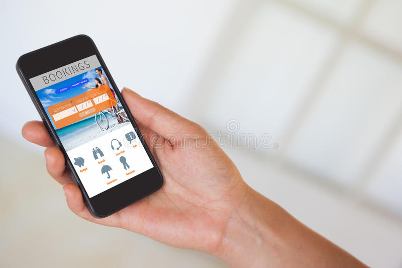 Imagen compuesta de la mano de la mujer que sostiene smartphone negro fotografía de archivo