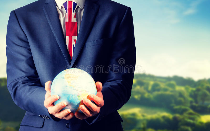Imagen compuesta de la mano del hombre de negocios que sostiene el globo terrestre foto de archivo libre de regalías