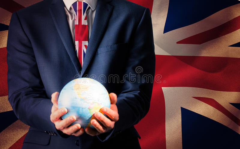 Imagen compuesta de la mano del hombre de negocios que sostiene el globo terrestre fotografía de archivo