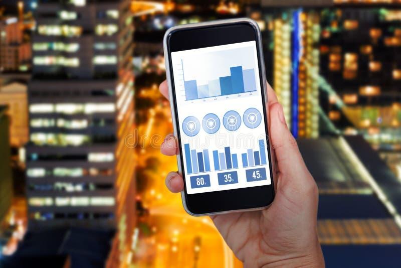 Imagen compuesta de la mano que sostiene el teléfono móvil contra el fondo blanco imagen de archivo libre de regalías