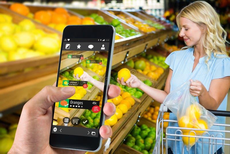 Imagen compuesta de la mano que sostiene smartphone fotografía de archivo libre de regalías