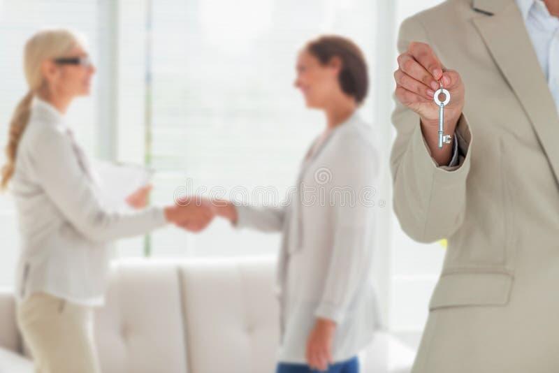 Imagen compuesta de la mediados de sección del ejecutivo de sexo femenino que muestra llave de la nueva casa fotografía de archivo