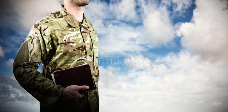 Imagen compuesta de la mediados de sección del soldado que sostiene los libros mientras que se coloca fotografía de archivo libre de regalías