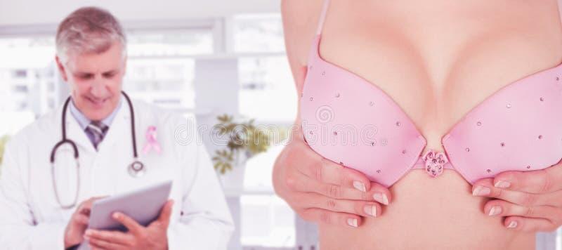 Imagen compuesta de la mediados de sección de la mujer en el pecho conmovedor del sujetador para la conciencia del cáncer foto de archivo libre de regalías
