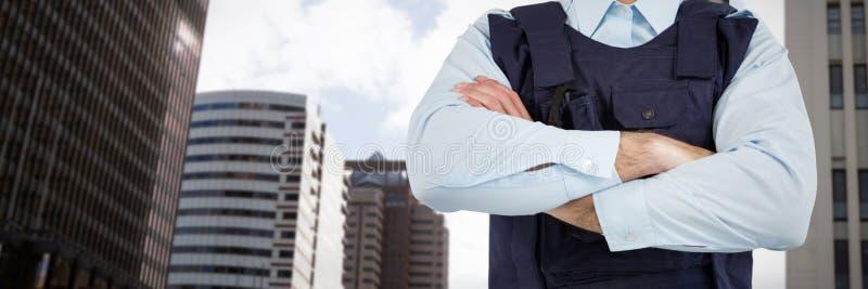 Imagen compuesta de la mediados de secci?n del agente de seguridad que se coloca con los brazos cruzados imagen de archivo libre de regalías