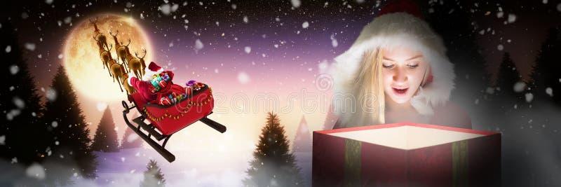Imagen compuesta de la mirada rubia festiva en el regalo que brilla intensamente foto de archivo libre de regalías