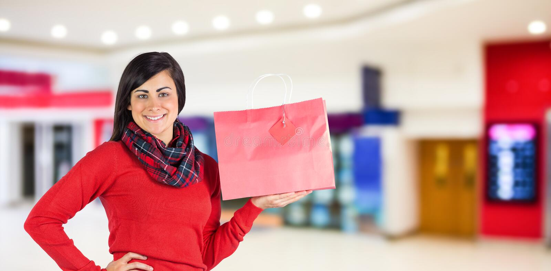 Imagen compuesta de la morenita sonriente que muestra el bolso rojo del regalo fotos de archivo libres de regalías