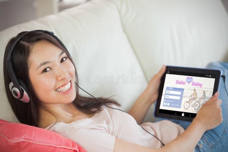 Imagen compuesta de la muchacha que usa su PC de la tableta en el sofá y escuchando la música que sonríe en la cámara imagen de archivo libre de regalías