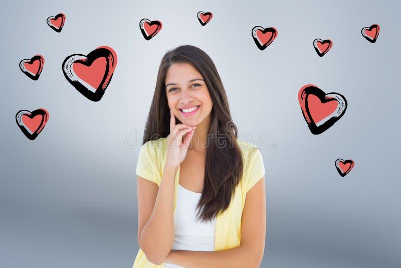 Imagen compuesta de la mujer casual feliz que piensa con la mano en la barbilla imagen de archivo