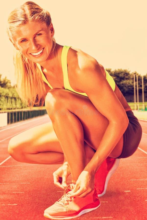 Imagen compuesta de la mujer deportiva que hace su cordón imagen de archivo libre de regalías