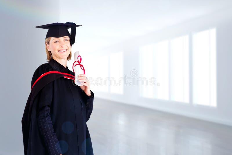 Imagen compuesta de la mujer graduada confiada que mira la cámara imágenes de archivo libres de regalías