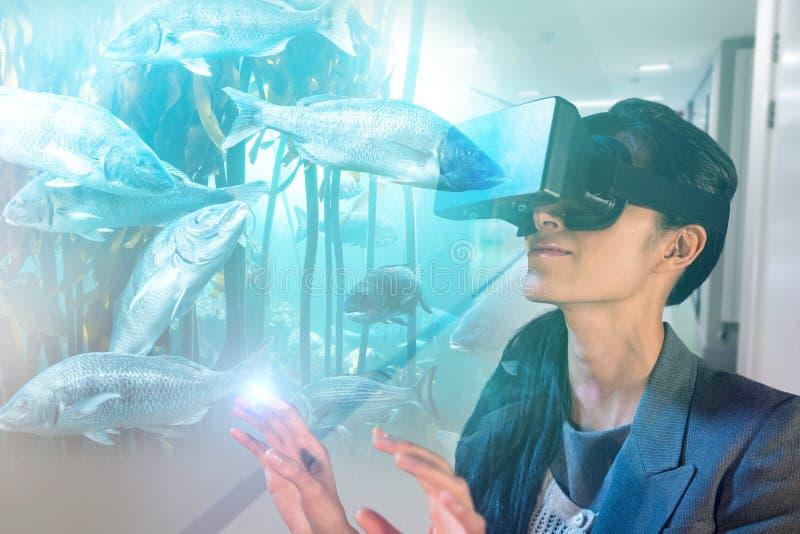 Imagen compuesta de la mujer joven que lleva los vidrios negros del simulador de la realidad virtual foto de archivo libre de regalías