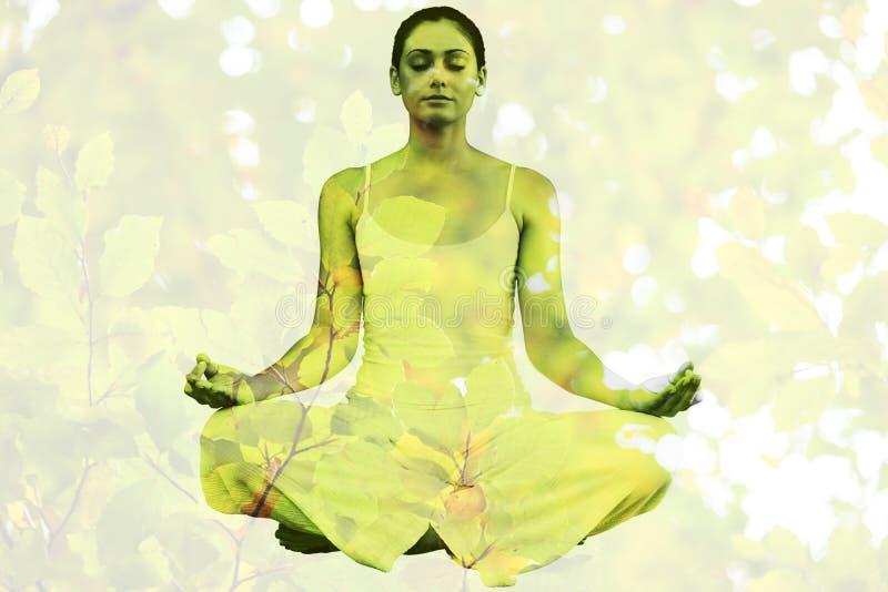 Imagen compuesta de la mujer pacífica en la sentada blanca en actitud del loto foto de archivo libre de regalías