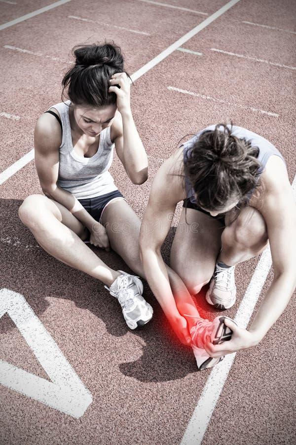 Imagen compuesta de la mujer que cuida sobre el corredor con lesión de los deportes imagenes de archivo