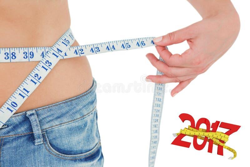 Imagen compuesta de la mujer que mide su cintura fotos de archivo