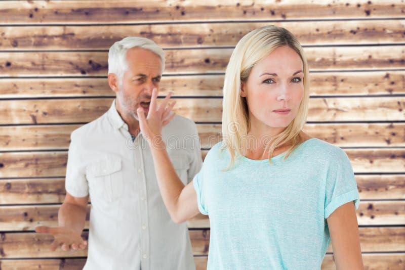 Imagen compuesta de la mujer que no escucha su socio enojado imagen de archivo libre de regalías