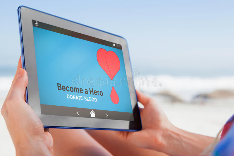 Imagen compuesta de la mujer que se sienta en la playa en silla de cubierta usando la PC de la tableta fotos de archivo libres de regalías