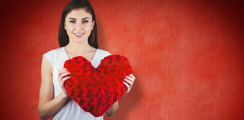 Imagen compuesta de la mujer que sostiene el amortiguador de la forma del corazón foto de archivo libre de regalías