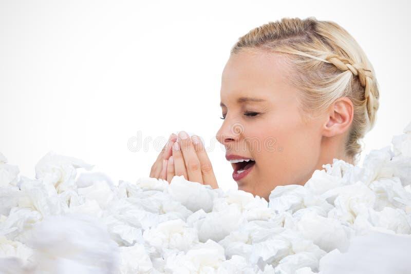 Imagen compuesta de la mujer rubia que estornuda con las manos delante de su cara imágenes de archivo libres de regalías