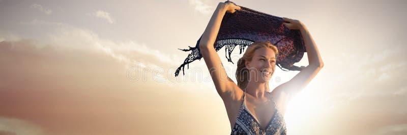 Imagen compuesta de la mujer sonriente que sostiene la bufanda en el aire foto de archivo