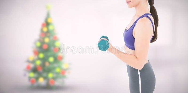 Imagen compuesta de la pesa de gimnasia de elevación de la mujer del ajuste fotografía de archivo libre de regalías