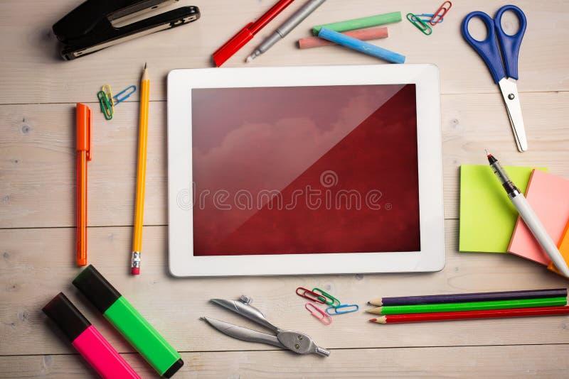 Imagen compuesta de la tableta digital en el escritorio de los estudiantes stock de ilustración