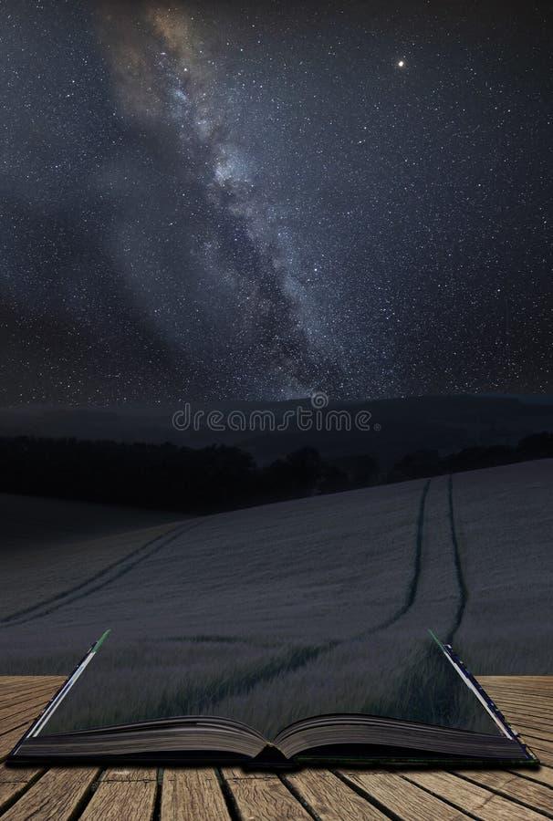 Imagen compuesta de la vía láctea vibrante sobre el paisaje del campo del verano del trigo que sale de las páginas del libro abie fotografía de archivo