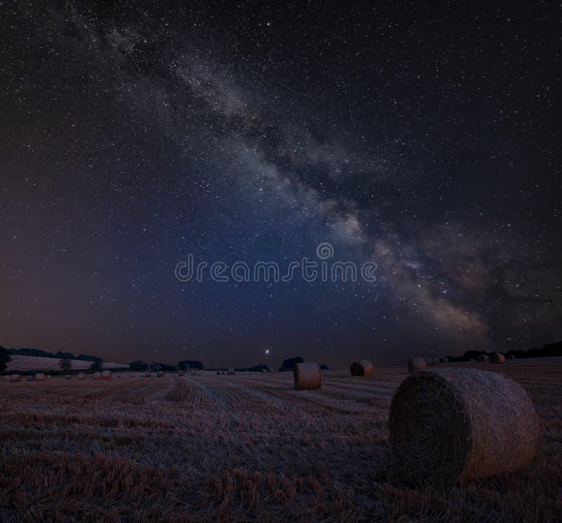 Imagen compuesta de la vía láctea vibrante sobre paisaje del heno precioso b foto de archivo libre de regalías