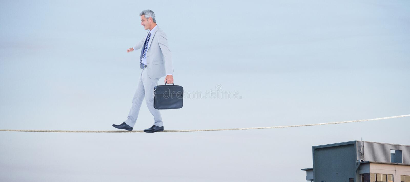 Imagen compuesta de la vista lateral del hombre de negocios que camina con la cartera sobre el fondo blanco fotos de archivo libres de regalías