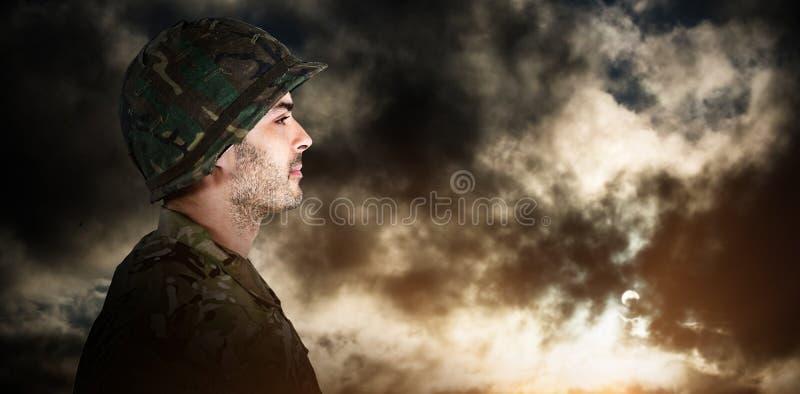 Imagen compuesta de la vista lateral del soldado confiado en la situación uniforme fotos de archivo libres de regalías