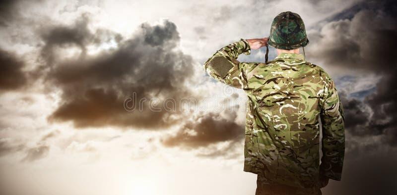 Imagen compuesta de la vista posterior de saludar militar del soldado foto de archivo