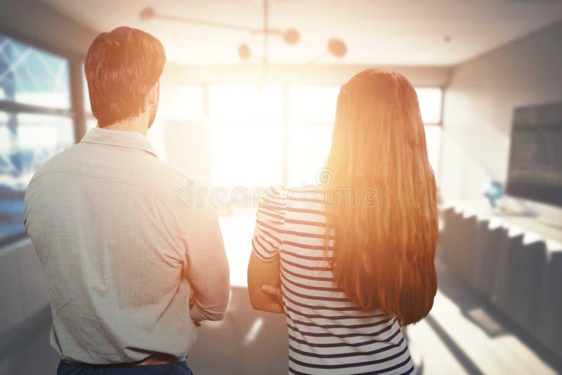 Imagen compuesta de la vista posterior de un hombre y de una mujer con los brazos cruzados imagen de archivo