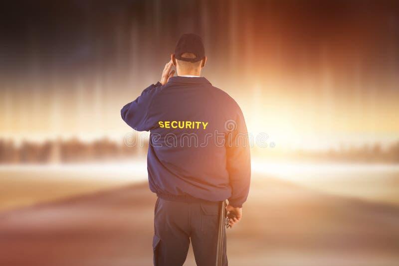 Imagen compuesta de la vista posterior del agente de seguridad que escucha el auricular fotografía de archivo