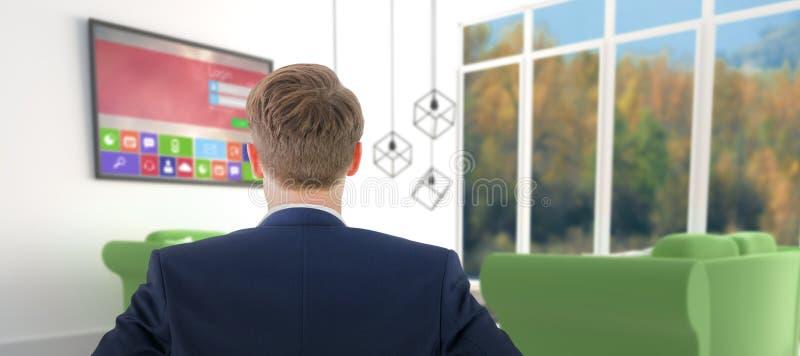 Imagen compuesta de la vista posterior del hombre de negocios que se coloca con las manos en wiast foto de archivo