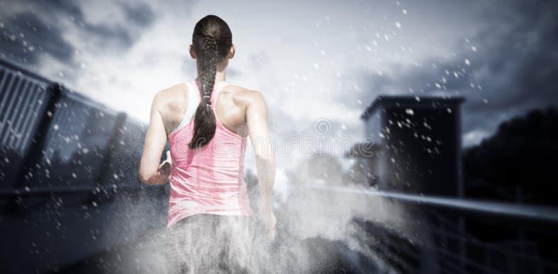 Imagen compuesta de la vista posterior de la mujer que corre contra el fondo blanco imagenes de archivo