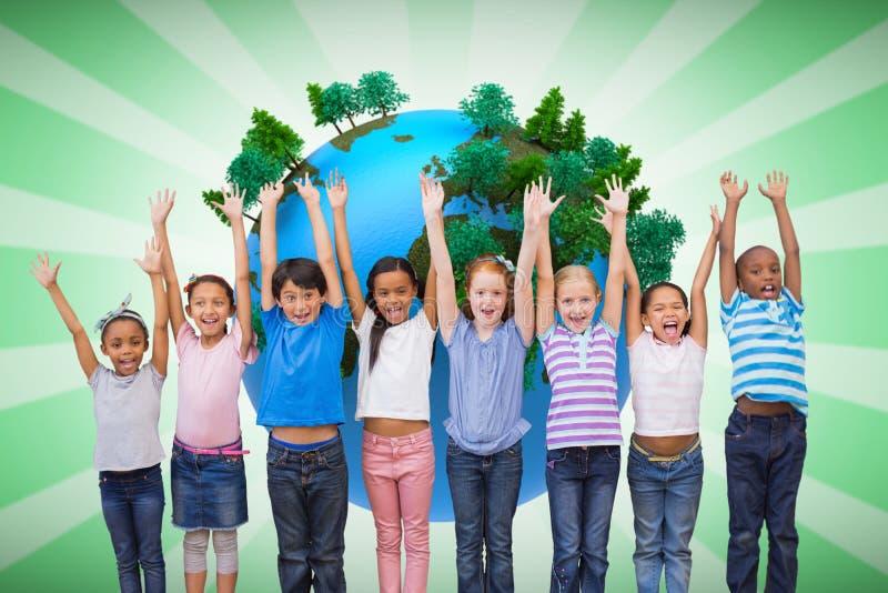Imagen compuesta de los alumnos lindos que sonríen en la cámara en sala de clase fotografía de archivo libre de regalías